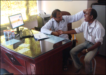 Dr. Vikram Chauhan is clinically diagnosing a patient using pulse and tongue examination techniques described in Ayurveda